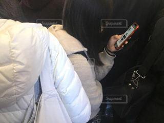朝の混雑した通勤電車の車内で携帯電話を操作する大人の女性の写真・画像素材[2798741]