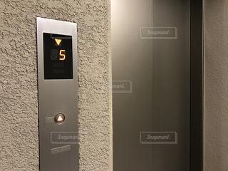 マンションの中にあるエレベーター乗り場のボタンとドアの写真・画像素材[2828964]