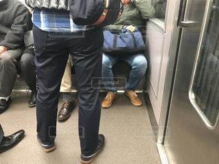 通勤電車の車内で座る男性と立つ男性の写真・画像素材[2893772]