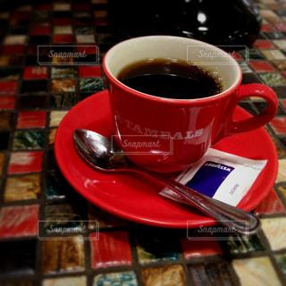 タイルカウンターの上に置かれた真っ赤なカップがステキなカフェのワンシーンの写真・画像素材[2945186]