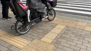 横断歩道て信号待ちをしている後ろに女の子を乗せた自転車を運転している母親の写真・画像素材[2988863]