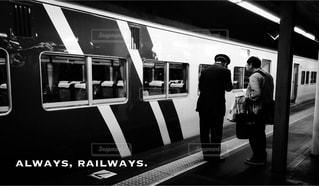 夜の東京駅で夜汽車に乗る乗客に案内をしている駅員の写真・画像素材[3004561]