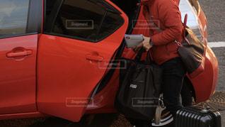 赤い車の後部座席から荷物を取り出す男性の写真・画像素材[3054064]