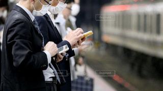 駅のホームで電車を待つ間、スマホを操作するマスク姿のサラリーマンの写真・画像素材[3091163]
