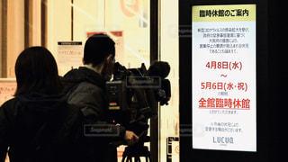 新型コロナウイルスのため掲出された臨時休業の告知を撮影するテレビ局のカメラマンの写真・画像素材[3091164]