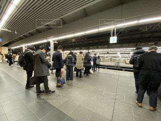 夜の大阪駅で帰りの電車を待つサラリーマンの行列の写真・画像素材[3109339]