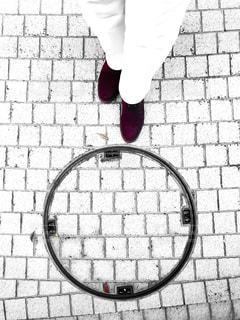 タイル目地の床面にあるマンホールと自分の靴の写真・画像素材[3122070]