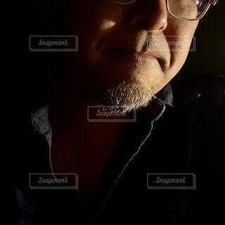 眼鏡をかけてカメラを見ている、髭をはやした男の顔の一部の写真・画像素材[3201933]