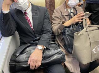 朝の通勤電車の中でマスク姿でスマホを操作する大人の女性の写真・画像素材[3307574]