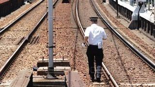 電車の線路脇の落下物を取りに行く駅員の写真・画像素材[3361718]