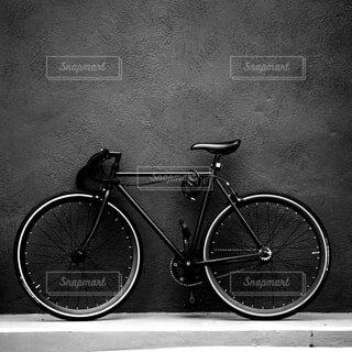 建物の脇に止めてある黒いクロスバイクの写真・画像素材[4413517]