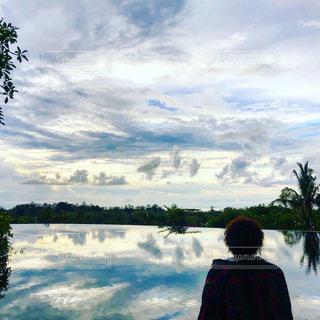 水の体の横に立っている人の写真・画像素材[1008965]