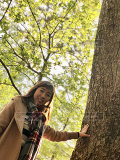 木の隣に立っている人の写真・画像素材[1008975]