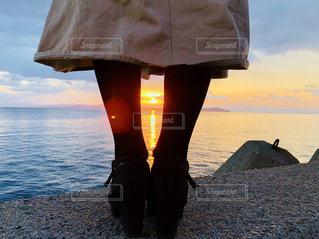 水の体の横に立っている人の写真・画像素材[1008976]