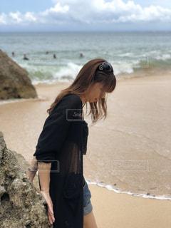 海の横にある砂浜に立っている人の写真・画像素材[1030089]