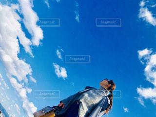 青い空を飛んでいる人の写真・画像素材[1073704]
