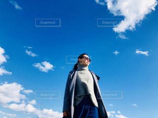 曇り青空の前に立っている人の写真・画像素材[1073705]