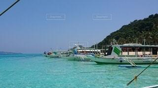 水の体の隣に座っている青と白のボートの写真・画像素材[2500320]
