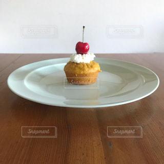 テーブルの上に座って赤と白のプレートの写真・画像素材[1234606]
