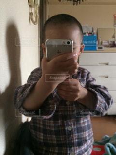 カメラにポーズを鏡の前で携帯電話を保持している男の写真・画像素材[879079]