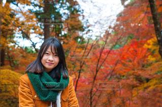 木の隣に立っている女性の写真・画像素材[1194174]