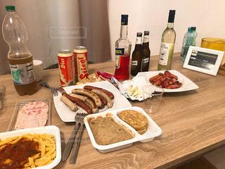 料理とテーブルの上にワインのボトルのプレートの写真・画像素材[1412446]