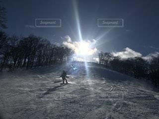 雪に覆われた斜面をスキーに乗る男 - No.957686