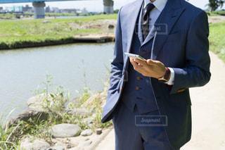 スマホを持つスーツの男性の写真・画像素材[1032099]