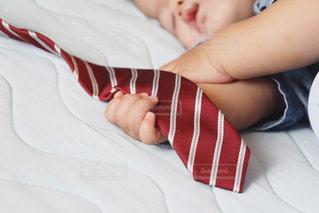 ネクタイを掴みながら眠る赤ちゃんの写真・画像素材[1290484]