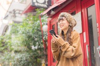 携帯電話で話している建物の前に立っている女性の写真・画像素材[1549016]