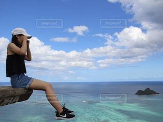 水の体の近くのビーチに座っている人の写真・画像素材[1012899]