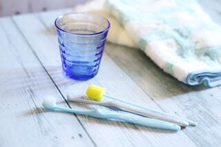 テーブルの上にガラスコップと歯ブラシ、オーラルケア用品。デンタルケア歯磨きイメージの写真・画像素材[3877924]