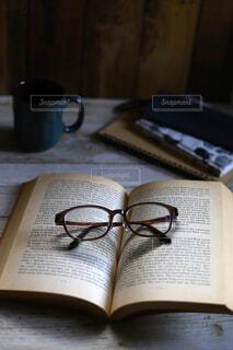 くつろぎの読書タイム、洋書のペーパーバッグと眼鏡の写真・画像素材[4156340]