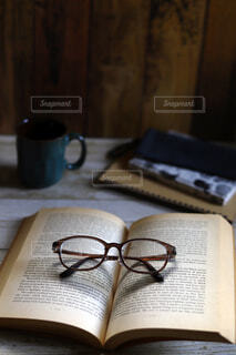 くつろぎの読書タイム、洋書のペーパーバッグと眼鏡の写真・画像素材[4156341]