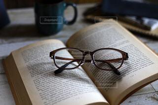 くつろぎの読書タイム、洋書のペーパーバッグと眼鏡の写真・画像素材[4156339]