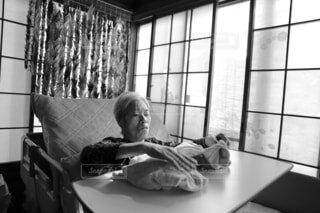 リクライニングした介護用ベッドでくつろぎながらタオルケットをいじる認知症のお婆ちゃんの写真・画像素材[4406773]