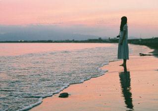 水の体の横に立っている人の写真・画像素材[897912]
