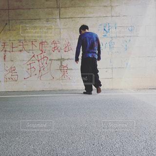 道路の側にスケートボードに乗っている若い男性の写真・画像素材[2141427]