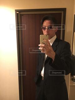 カメラにポーズ鏡の前に立っている男の写真・画像素材[1679962]