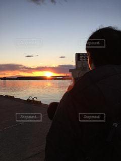 水の体の横に立っている人の写真・画像素材[901476]