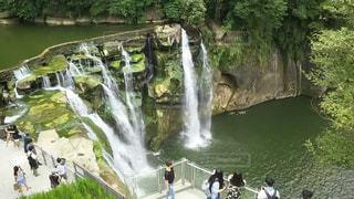 滝の隣に川に沿って歩く人々 のグループの写真・画像素材[901480]
