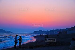 背景の夕日とビーチの上を歩く人々 のグループ - No.1115949