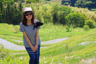 緑豊かな緑のフィールドに立っている人の写真・画像素材[1224342]