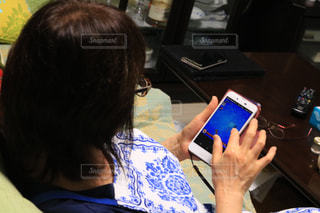 携帯電話を見てテーブルに座っている人々 のグループの写真・画像素材[1437348]