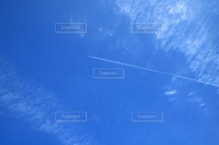 澄んだ青い空を飛んでいる飛行機の写真・画像素材[1635569]