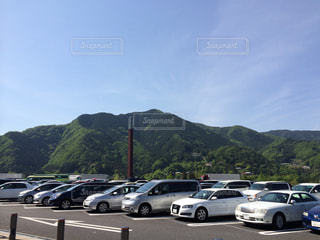 背景の山の駐車場に停まっている車の写真・画像素材[990498]