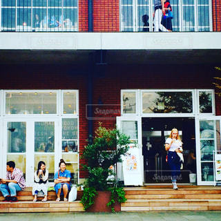 店の窓の前に座っている人々 のグループ - No.772576