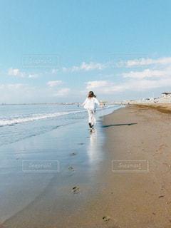 水の体の横にビーチの上を歩く男 - No.925710