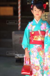 建物の前に立っている赤いドレスを着ている男の子 - No.745450