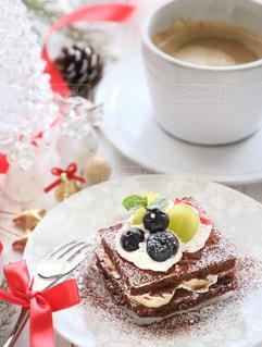 コーヒー カップの横にある皿の上のケーキの一部の写真・画像素材[878440]